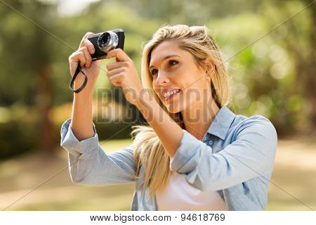 pretty blonde woman taking picture with camera outdoors