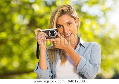 smiling pretty blond woman with a camera outdoors