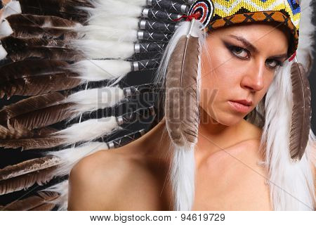 Beautiful woman in native american costume with feathers .