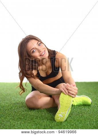 Woman doing stretching exercises on the green grass .