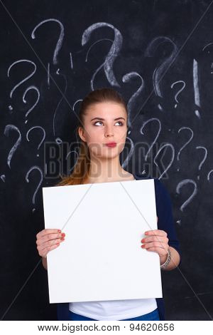 Young girl with question mark holding a blank on a gray background .