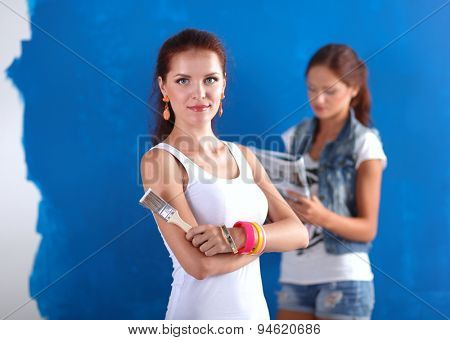 Two beautiful young woman doing wall painting .