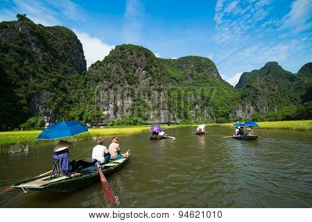 Unidentified travellers with rower guides in a boat trip visiting Tam Coc in Ninh B