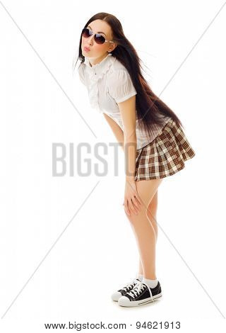 Modest school girl in plaid skirt and sneakers isolated