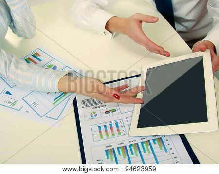Business colleagues sitting together at table and viewing documents from clipboard