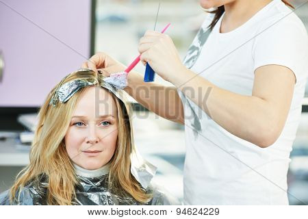 Highlight. Hairdresser woman making highlighting coloring of female client hair in beauty parlour hairdressing salon