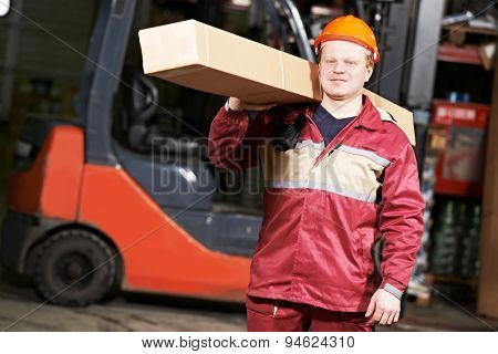 young warehouse worker in uniform in front of forklift stacker loader with box