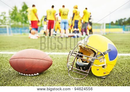 American football helmet and ball lying on field