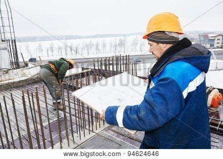 concreting works. foreman with blueprint plan in front of concrete reinforcement at construction site. Worker is sharp, plan slightly blurred doe to wind