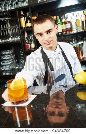 young barman worker at bartender desk in restaurant bar with coctail
