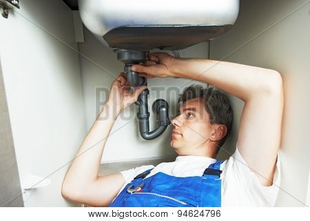 Young plumber worker repair or installing kitchen sink with spanner