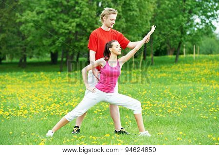 Young fitness woman and male instructor doing physical stretching exercises during outdoors sport training