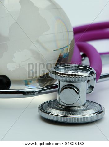 Stethoscope next to glass globe world map, isolated on white background