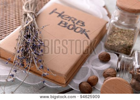 Dry lavender with nutmeg and book on table close up