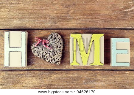 Decorative letters forming word HOME with decorative heart on wooden background