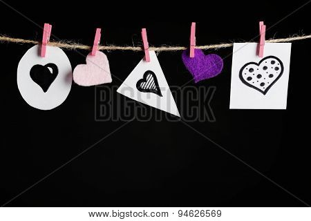 Bright hearts hanging on rope on dark background