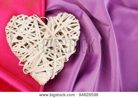 Wicker heart on fabric background