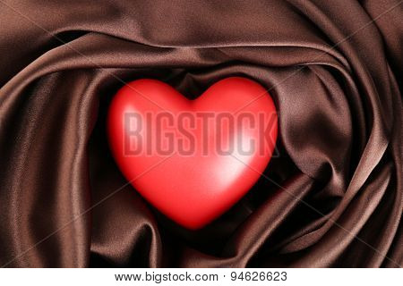 Red heart on fabric background
