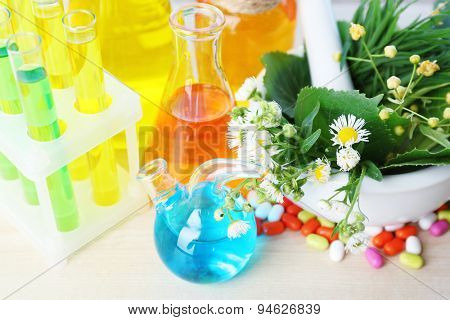 Herbs in mortar, test tubes and pills,  on table background