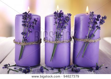 Candles with lavender flowers on bright background