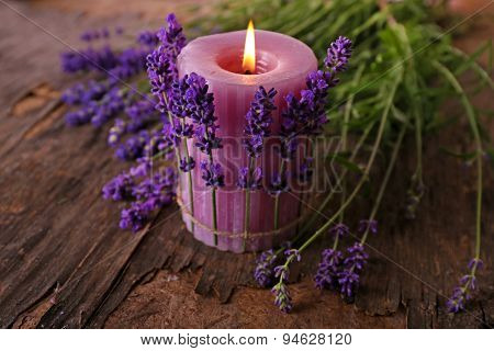 Candle with lavender flowers on table close up