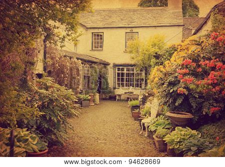 Garden at the front of  old house, Lake District, Cumbria, UK.  Photo in retro style.  Added paper texture.