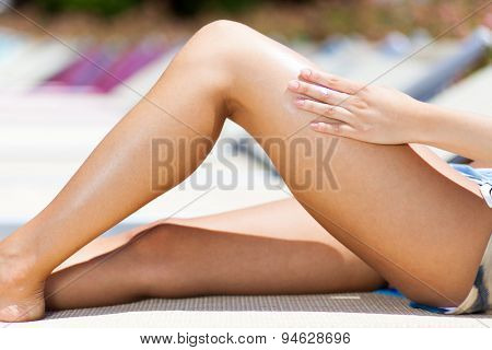 Woman applying sun screen on her legs