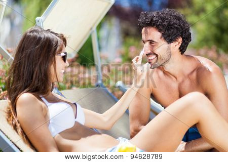 Woman applying tan screen on her boyfriend's nose