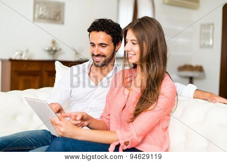 Portrait of an happy couple using a tablet. Shallow depth of field, focus on the man