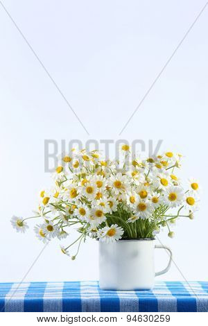 Beautiful bouquet of daisies in cup on light background