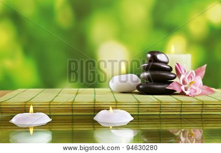 Spa still life with flowers and candlelight on green blurred background