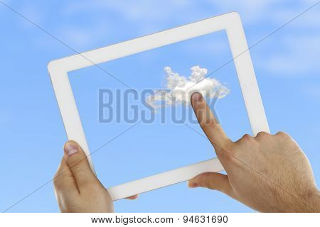 Hand touching cloud on tablet on sky background