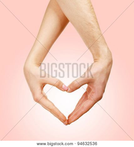 Hands in shape of heart on light background