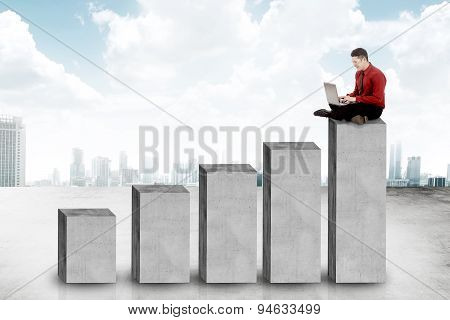 Asian Business Man Sitting On The Chart Block