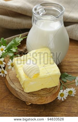 fresh yellow butter with a jug of milk, rustic still life