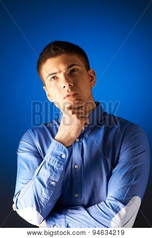 Portrait of thoughtful man against blue background
