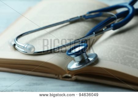 Stethoscope on open book close up