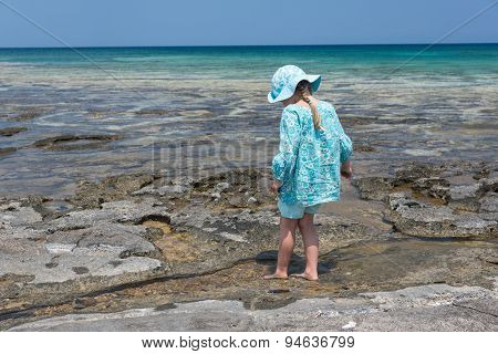 Girl In Blue Hat And Dress Walking Into Sea