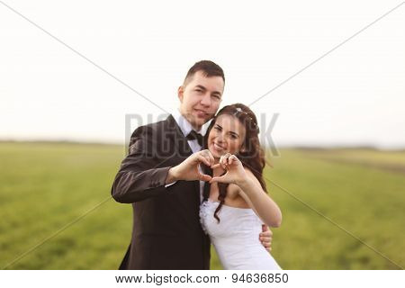 Bride And Groom Making Love Sign
