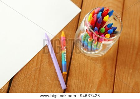 Colorful pastel crayons with white sheet of paper on wooden background