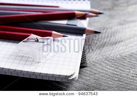 Stationery with red crayons on wooden table, closeup