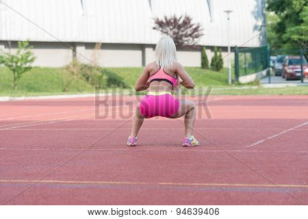 Attractive Female Doing Kettle Bell Exercise Outdoor