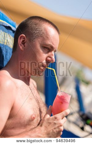 Handsom Man Sipping A Drink At A Hotel Swimming Pool