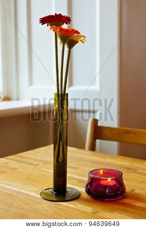 Vase with flowers and candle on table in cafe