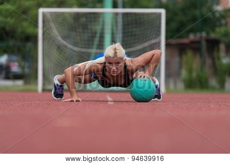 Young Woman Exercising Push-ups On Medicine Ball Outdoor