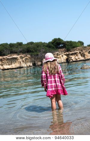 Small Girl In A Hat And Dress Standing In A Shallow Sea Water