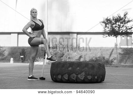 Sexy Woman With Hammer And Tire