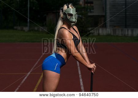 Young Woman With Hammer And Gas Mask