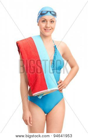 Young female swimmer in a blue swimsuit carrying a towel over her shoulder and looking at the camera isolated on white background