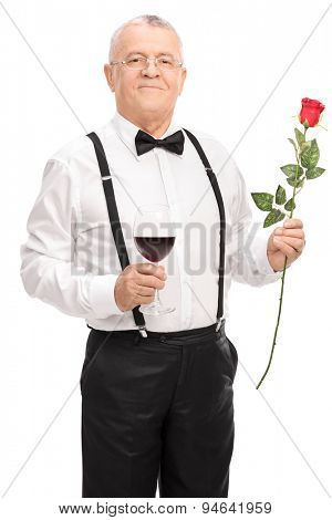 Vertical shot of a romantic senior gentleman holding a glass of red wine and a red rose isolated on white background